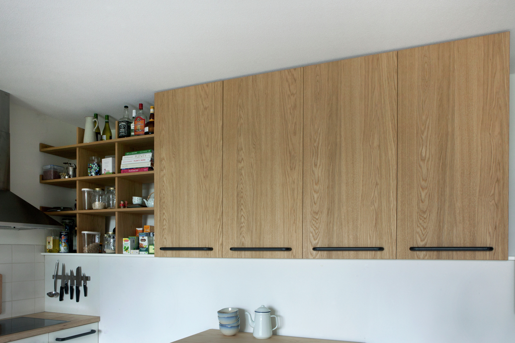 Kitchen cupboard and shelves made from oak covered mdf with metal handles.